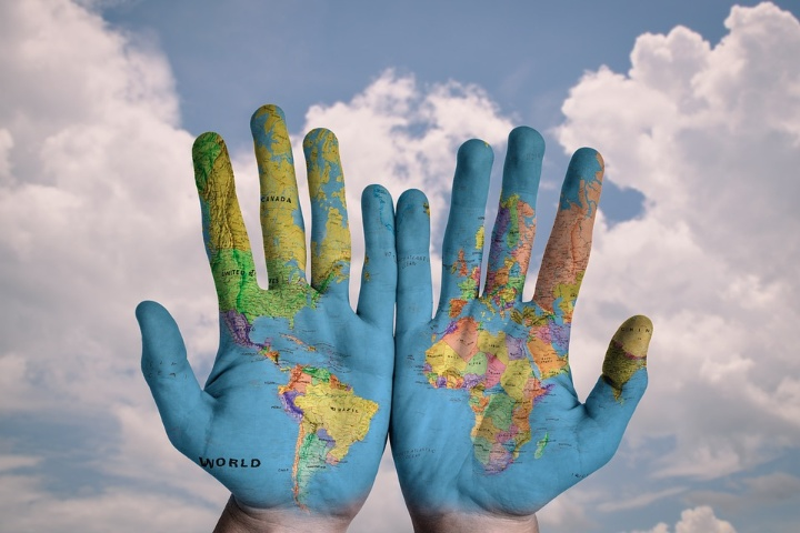 The picture shows two hands on which the world map is shown.